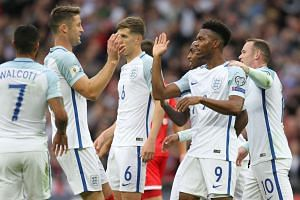 England's striker Daniel Sturridge (2nd R) celebrates with teammates after scoring the opening goal.