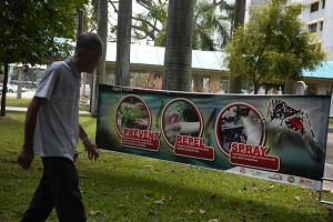 "A man walks pass a ""fight dengue"" banner in Aljunied Crescent."