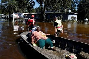 Rescue personnel evacuate a resident by boat after flood waters from Hurricane Matthew cover the downtown area in Nichols, South Carolina, on Oct 10, 2016.