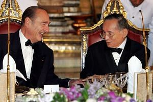 This file photo taken on Feb 17, 2006 shows then French President Jacques Chirac (right) speaking to Thai King Bhumibol Adulyadej at the start of a gala dinner at the Royal Palace in Bangkok.