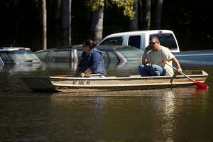 People in a small boat drift past flooded cars as a result of Hurricane Matthew in Lumberton, North Carolina, Oct 11, 2016.