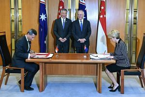 Singapore's Minister for Foreign Affairs Vivian Balakrishnan (left) and his Australian counterpart Julie Bishop (right) sign a memorandum of understanding at Parliament House, as Singapore's Prime Minister Lee Hsien Loong (second from left) and his A