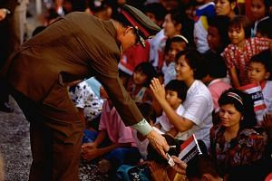 King Bhumibol greeting his people and giving out cash, in this photo taken in 1990. He and Queen Sirikit gave out tens of thousands of blankets, towels, clothes and school uniforms to Thais every year on their tours, during which he actively engaged