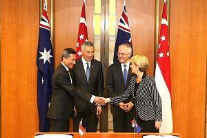 Singapore Foreign Minister Vivian Balakrishnan and his Australian counterpart Julie Bishop acknowledging the signing of a memorandum of understanding on science and innovation, one of the four CSP agreements, in Canberra's Parliament House yesterday,