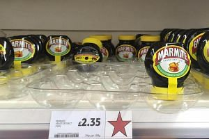 Jars of Marmite, a brand of Unilever, are displayed for sale on a shelf at a Tesco supermarket in Basildon, Britain on Oct 13, 2016.