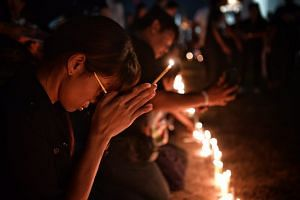 Mourners pray during a candlelight vigil for the late Thai King outside the walls of the Wat Phra Kaew on Oct 15, 2016.