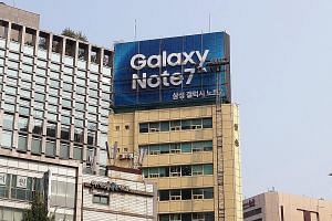 A Southwest Airlines passenger's Note7 replacement phone caught fire inside a plane in the US earlier this month. Workers taking down a billboard for Samsung Electronics' Galaxy Note7 from a building in Seoul on Friday. The company has yet to identif