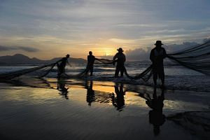 Indonesian fishermen clean a net in Banda Aceh, Aceh province, after overnight fishing.