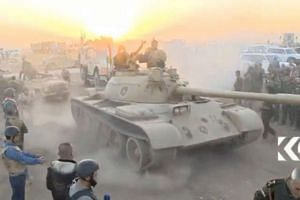 Tanks move past soldiers east of Mosul as the sun sets on Oct 17, 2016.