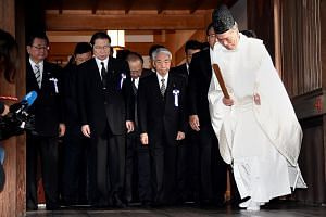 A Shinto priest leads a group of Japanese lawmakers at the controversial Yasukuni Shrine, in Tokyo on Oct 18, 2016.