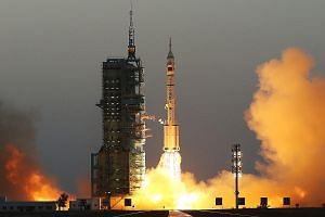 Far left: The Long March-2F rocket, carrying the Shenzhou-11 spacecraft, taking off from Jiuquan, Gansu province, yesterday. Left: Astronauts Jing (at right) and Chen in the Shenzhou-11 spacecraft.
