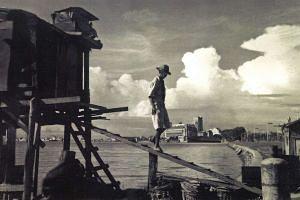 A man steps out of his house built on stilts at the Merdaka Bridge. In the distance is the Fullerton Building in Singapore in the 1960s or 70s.