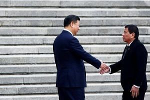 Philippines President Rodrigo Duterte and Chinese President Xi Jinping shake hands as they attend a welcoming ceremony at the Great Hall of the People in Beijing, China on Oct 20, 2016.
