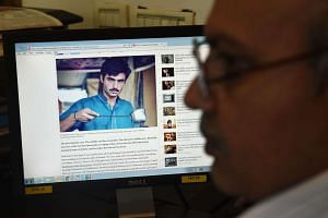 A Pakistani man looks at images of 'chai wala' Arshad Khan, who became famous on social media, on the internet at his office in Islamabad on Oct 19, 2016.