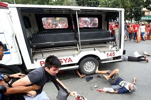 Protesters lying on the ground yesterday after being hit by a police van during a rally in front of the US embassy in Manila. The van rammed into and ran over baton-wielding protesters.