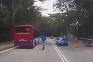 Above: An e-scooter user is seen riding beside a bus along Aljunied Road in a video taken last Friday that went viral.