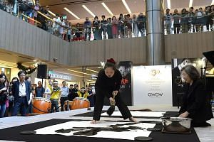 Calligrapher Shoko Kanazawa working on her second calligraphy work - de, or virtue - at Paragon Shopping Mall yesterday. The event, SJ50, was organised to celebrate 50 years of diplomatic relations between Singapore and Japan, as well as to embrace t