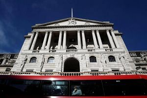 A bus travels past the Bank of England in London.