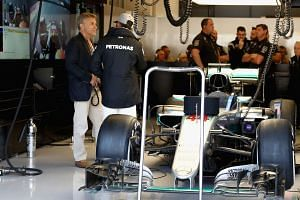 Hamilton chats with actor Christoph Waltz in the garage during final practice for the US grand prix on Oct  22, 2016.