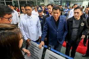 Philippine President Rodrigo Duterte walks through the terminal at the Davao International Airport after arriving back from a state visit to Brunei and China.