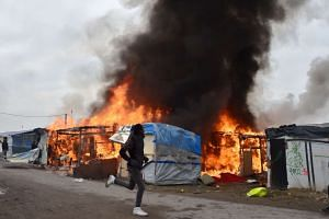 """A migrant runs next to a makeshift shelter on fire at the """"Jungle"""" migrant camp in Calais on Oct 26, 2016."""