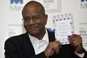 Man Booker Prize winner Paul Beatty poses for photos with his novel The Sellout at the Guildhall in London.