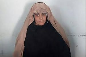 Afghan Sharbat Gula, the 'Afghan Girl' who appeared on the cover of a 1985 edition of National Geographic magazine, waits ahead of a court hearing in Peshawar.
