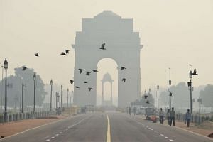 Indian pedestrians walk near the India Gate monument amid heavy smog in New Delhi on Oct 28, 2016.