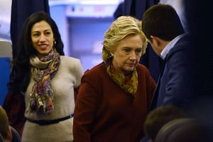 US Democratic presidential nominee Hillary Clinton chatting with her staff, including aide Huma Abedin (left), onboard her plane in White Plains, New York, on Oct 22, 2016.