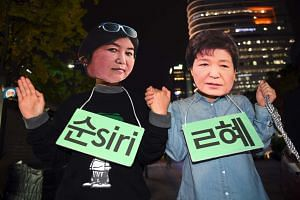 Protesters wearing masks of South Korean President Park Geun Hye (right) and her confidante Choi Soon Sil posing for a performance during a rally denouncing a scandal over President Park's aide in Seoul on Oct 27, 2016.