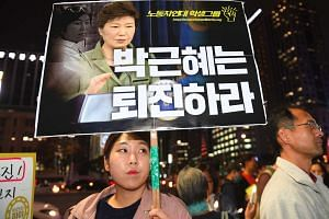 A protestor holds a placard showing portraits of South Korean President Park Geun Hye (centre) and her confidante Choi Soon-Sil during a rally denouncing a scandal over President Park's aide.