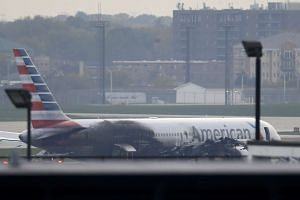 Soot covers the fuselage of an American Airlines jet that blew a tire, sparking a fire and prompting the pilot to abort takeoff before passengers were evacuated from the plane via emergency chute, at O'Hare International Airport in Chicago, Illinois,