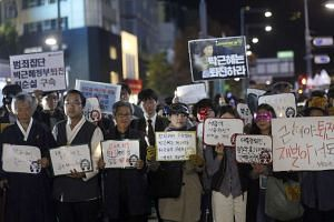 South Korea citizens and members of civic groups holding placards during a protest, demanding President Park Geun Hye to step down, in downtown Seoul on Oct 27, 2016.