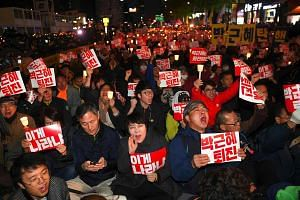"South Korean protesters hold up signs reading ""Step down Park Geun-Hye!"" and shout slogans during a candle-lit rally in central Seoul on October 29, 2016, denouncing President Park over a high-profile corruption and influence-peddling scandal involvi"