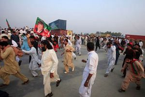 Supporters of Pakistani opposition leader Imran Khan run from tear gas as clashes begin between police and protesters in Swabi, Pakistan on Oct 31, 2016.