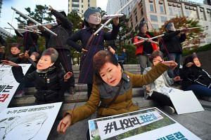 Protesters wearing masks of South Korean President Park Geun Hye (front) and her confidante Choi Soon Sil (back) in Seoul on Oct 29, 2016.