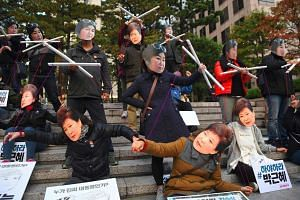 Protestors wearing masks of South Korean President Park Geun Hye (bottom) and her confidante Choi Soon Sil.