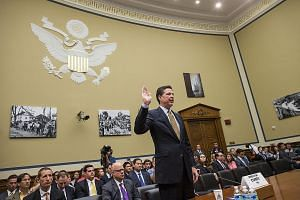 Mr Comey being sworn in to testify on Capitol Hill in Washington on July 7. The FBI director has been accused by Clinton allies of trying to influence the presidential election on Nov 8, by revealing that the FBI was restarting a probe into the forme