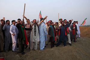 Supporters of Pakistan opposition leader Imran Khan shout slogans at a spot where police blocked the highway with shipping containers in Swabi, Pakistan, on Oct 31, 2016.