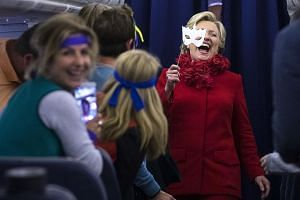 Mrs Clinton joking with her staff on a flight to Erlanger, Kentucky, during Halloween, which fell on Monday. Her campaign is working to contain the damage from FBI director James Comey's announcement that the agency was restarting a probe into the fo