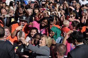Mrs Clinton taking a wefie during a rally on Sept 29 in Des Moines, Iowa. A win at the ballot box for her will boil down to voter turnout, say experts.