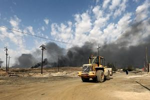 Smoke rise from burning oil fields which were damaged during the fighting between Iraqi forces and ISIS fighters in Qayara town, some 50km south of Mosul.