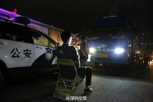 Shenzhen police are punishing traffic offenders by making them stare at high beam headlights.