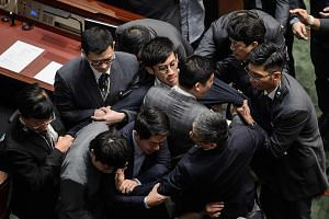 Mr Sixtus Leung (centre, wearing glasses) being restrained by security officers after attempting to recite the oath at the Legco Chamber yesterday. Describing the acts of Mr Leung and Ms Yau as violent and premeditated, the Legco president strongly c
