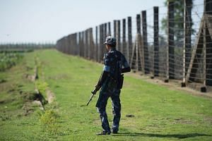 An armed Myanmar border guard patrols the border fence along the river dividing Myanmar and Bangladesh located in Maungdaw, Rakhine State, on Oct 15, 2016.