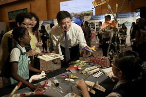 Minister for Education (Schools) Mr Ng Chee Meng speaking to Nur Sabrina Rahim (bottom right, back to camera), 10, fom Rainbow Centre, Yishun Park School, after the opening of the Special Education (Sped) Conference 2016, at Resorts World Sentosa.