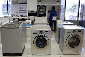 Samsung washing machines are seen as an employee inspects refrigerators at a Samsung display store in Johannesburg, on Oct 3, 2013.
