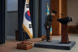 Above: South Korean President Park Geun Hye bowing before delivering an address to the nation at the presidential Blue House in Seoul yesterday. She said that she would do her best to cooperate with the prosecution. Below: The woman at the centre of