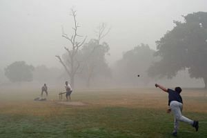 A group of men playing cricked in heavy smog in New Delhi on Nov 6, 2016.