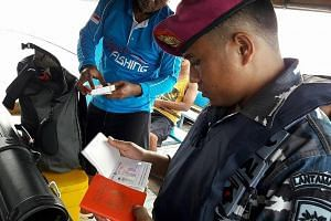 A member of the Indonesian Navy inspecting the passports of the Singaporean anglers caught sailing in an unlicensed boat off Bintan.